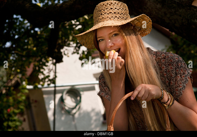 Mid adult woman eating an apple in the garden, Munich, Bavaria, Germany - Stock-Bilder