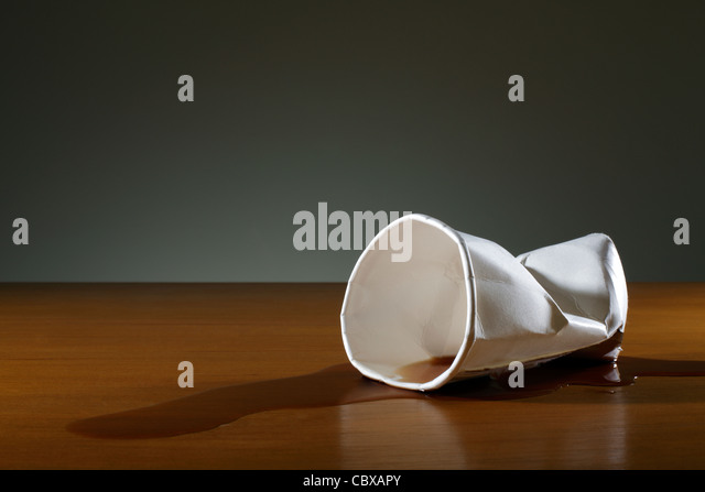 Crumpled paper cup on desk - Stock Image