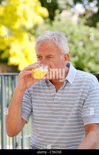 Diabetic man drinking a glucose drink. - Stock Image
