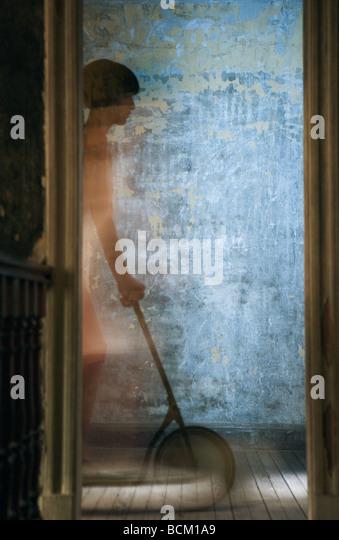 Woman riding scooter on hardwood floor, seen through doorway, blurred motion - Stock-Bilder