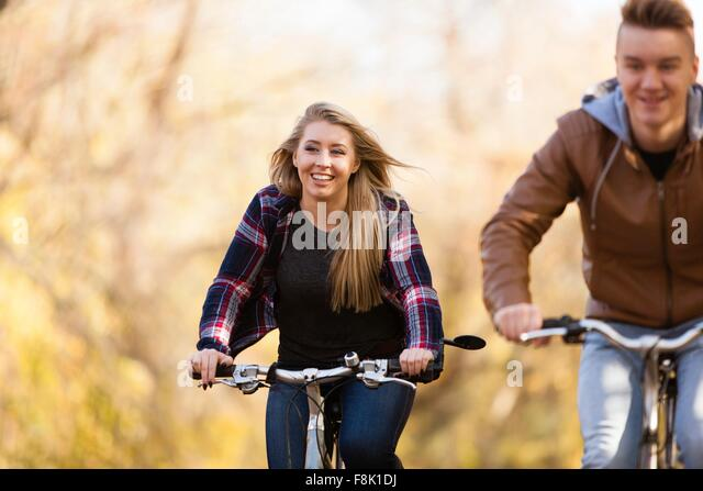 Teenage boy and adult sister cycling through autumn forest - Stock Image