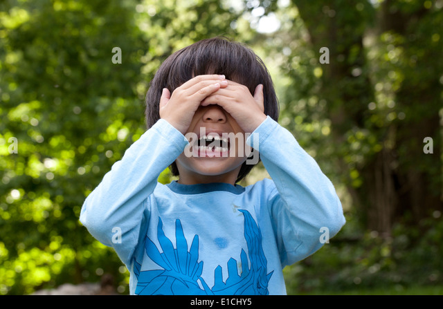 Boy, aged 5, crying with hands over face - Stock Image