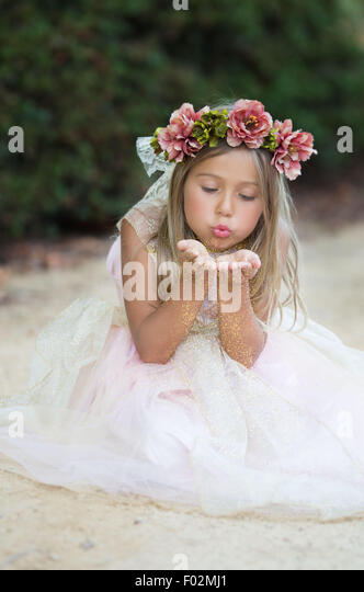 Girl sitting on beach blowing glitter - Stock Image
