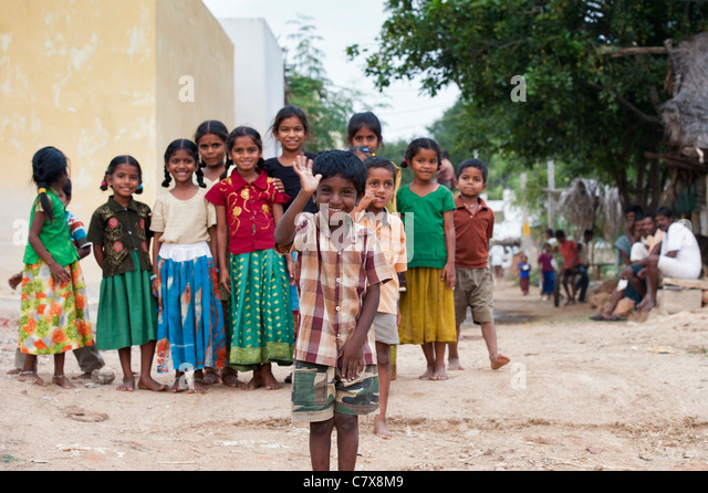Happy young rural Indian village boy laughing waving in front of a group of  village children. selective focus - Stock Image