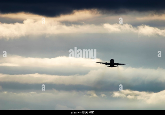 Plane in flight in a dramatic cloudscape. - Stock Image