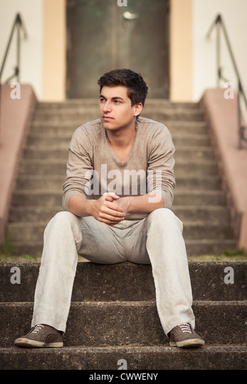 Man sitting on front steps - Stock Image