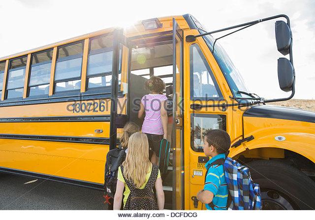Schoolchildren boarding school bus going for field trip - Stock Image