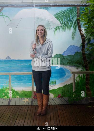 Woman under umbrella with beach backdrop - Stock Image