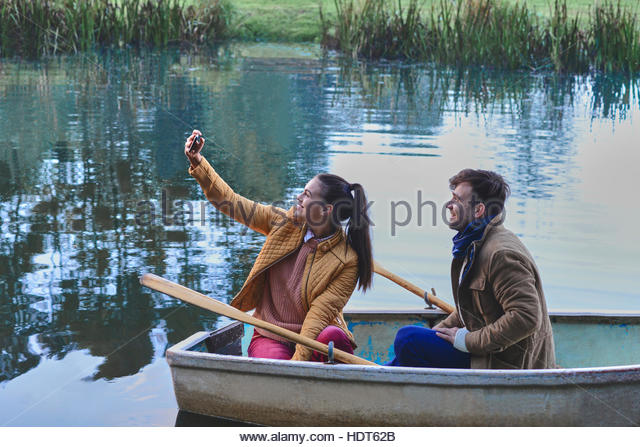 Young woman taking selfie while in row boat with her boyfriend. - Stock Image