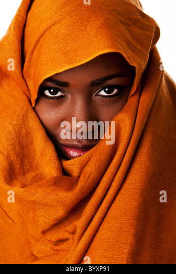 Beautiful mysterious african nomadic female face in ocher Earth tone head wrap scarf looking. - Stock Image