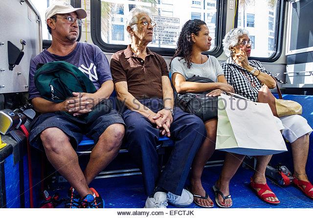 Miami Beach Florida Miami-Dade Metrobus public transportation South Beach Local passengers riders sitting Hispanic - Stock Image