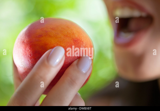 Woman holding peach to mouth - Stock Image