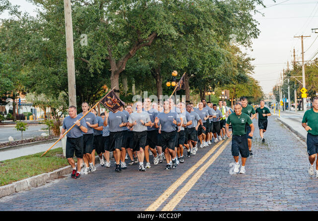 Law enforcement academy cadets running in formation through the streets of Tampa, Florida USA, part of police training. - Stock Image