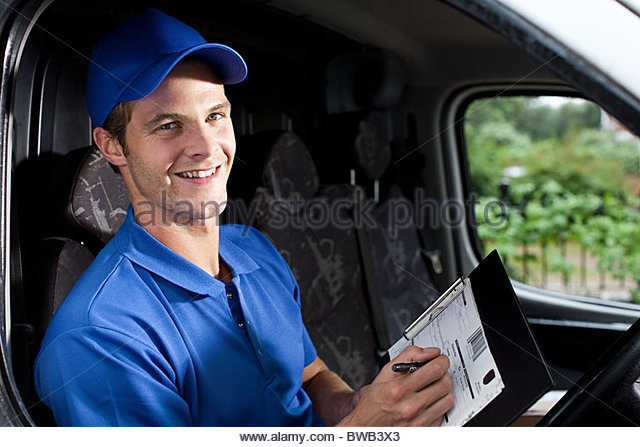 Delivery man in van writing on clipboard - Stock Image