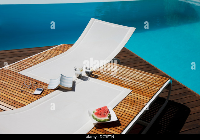 Book, mp3 player, water and watermelon on lounge chairs at poolside - Stock Image