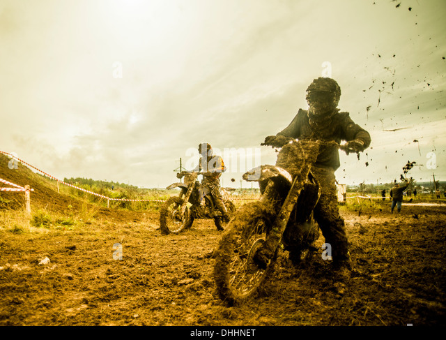 Two boys racing motorcycles at motocross - Stock Image