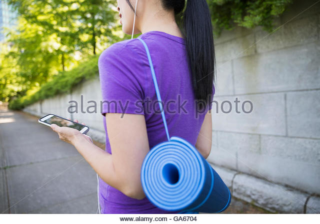 Pregnant woman with yoga mat and headphones using cell phone - Stock Image