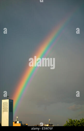 Intense rainbow with church tower - Stock Image