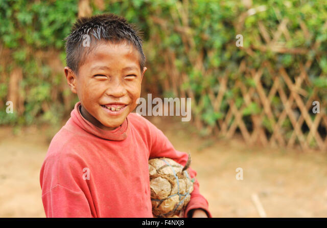 Nagaland, India - March 2012: Happy young footballer with self-made ball smiles at camera, Nagaland, remote region - Stock Image