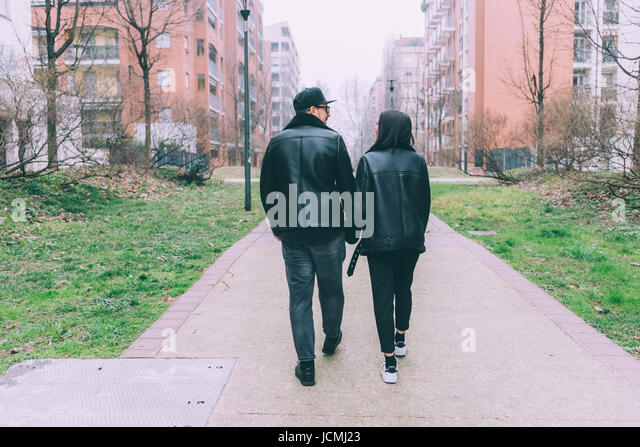 Back view of young couple walking outdoor holding hands - love, relationship, everyday life concept - Stock-Bilder
