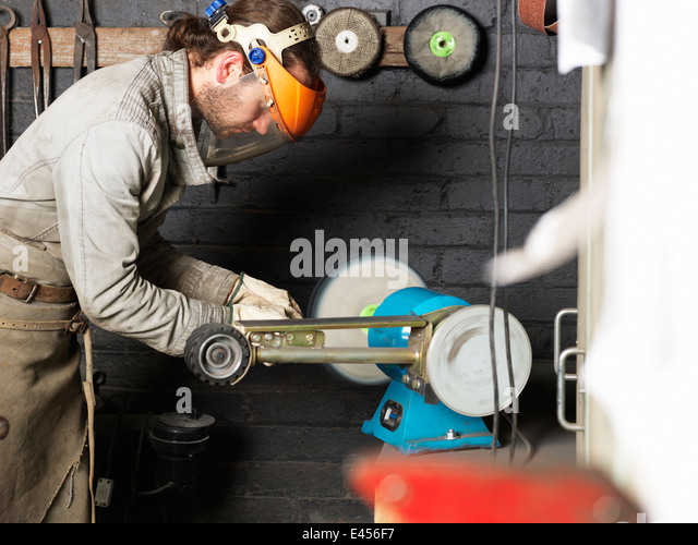 Blacksmith working on machine in workshop - Stock Image