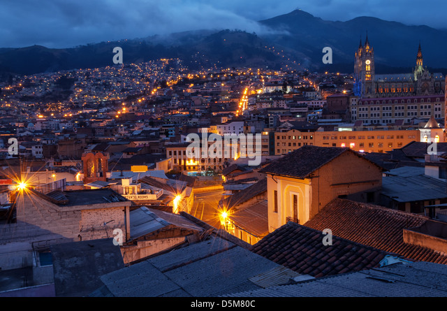 Quito, Ecuador old town and basilica at night with mountains in the background - Stock Image