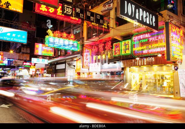 Neon signs and car light trail in Tsim Sha Tsui, Kowloon, Hong Kong, China. - Stock Image