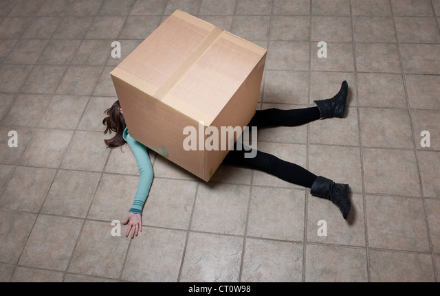 Teenage girl lying under cardboard box - Stock Image
