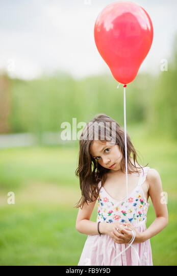 Sweden, Vastmanland, Bergslagen, Cute girl (6-7) holding red balloon - Stock Image