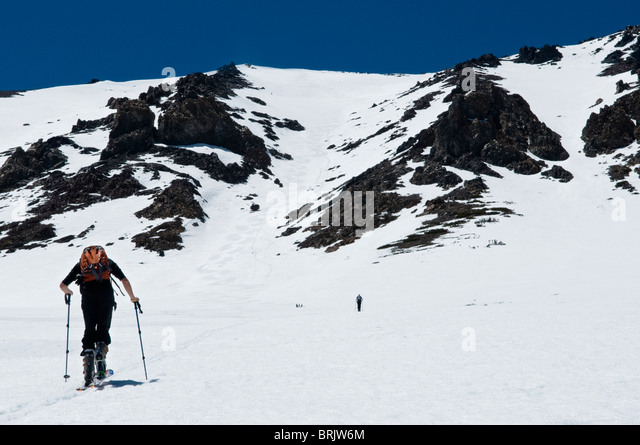 During his last ski tour for the season, a young man skins up for the summit in June Lake, California. - Stock Image