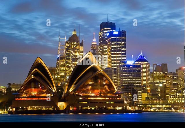 Australia, Sydney, View across Sydney harbour to Sydney Opera House & skyline at dusk - Stock Image