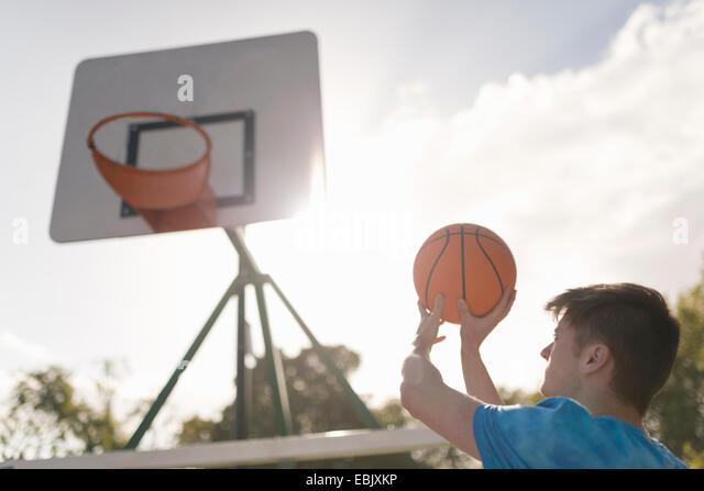 Young man aiming to throw basketball into basketball hoop - Stock Image