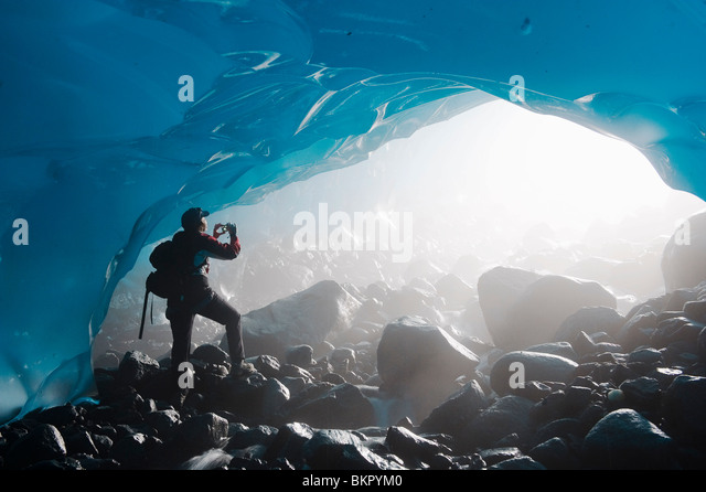 A hiker takes a photograph of the entrance of an ice cave from the inside of the Mendenhall Glacier, Southeast Alaska, - Stock Image
