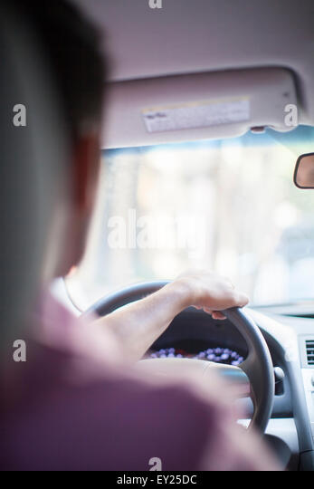 Over the shoulder view of young businessman driving car - Stock Image