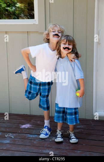 A brother and sister are standing together wearing fake mustaches. - Stock Image