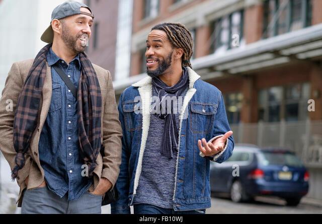 Smiley homosexual couple walking down street - Stock-Bilder