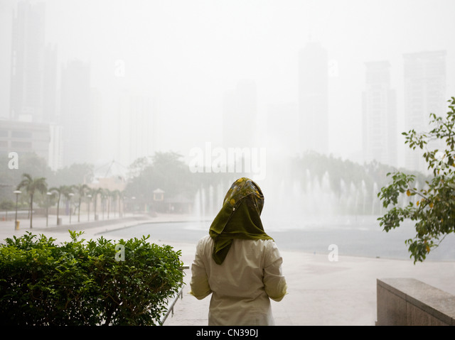 Young muslim woman waiting for rain to end, Kuala Lumpur, Malaysia - Stock Image