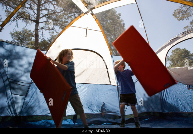 Two boys playing with inflatable mattresses in a tent - Stock-Bilder
