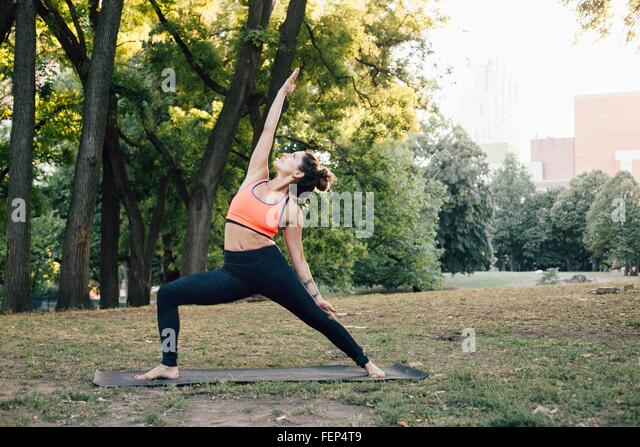 Woman in Peaceful Warrior pose (Parivrtta Virabhadrasana) - Stock Image