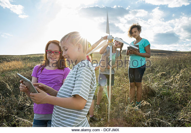 Kids using digital tablet with friends analyzing wind turbine model - Stock Image