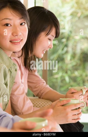 Two female office workers holding coffee cups and smiling - Stock Image