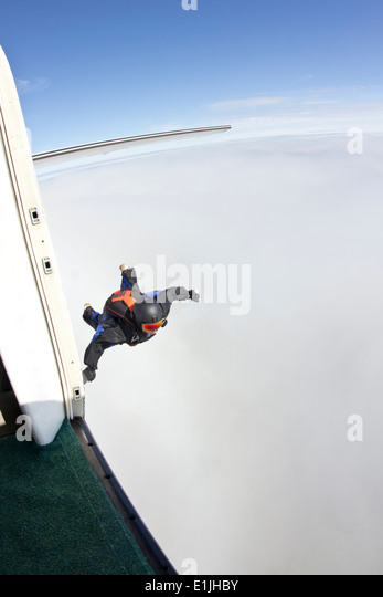 Mid adult man mid air preparing to fly in wingsuit - Stock Image