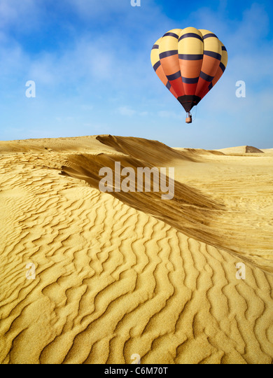 hot air balloon floating over sand dunes at Oceano Dunes, Pismo Beach, California - Stock Image