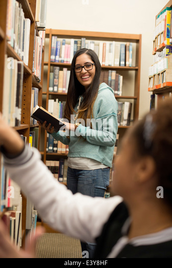 Young women choosing books in library - Stock Image