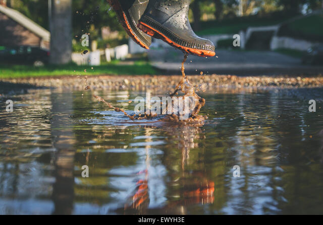 Low angle close-up of a boy jumping in a muddy puddle - Stock Image