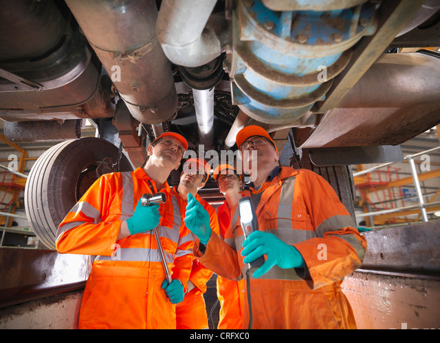 Engineer teaching apprentices in factory - Stock Image