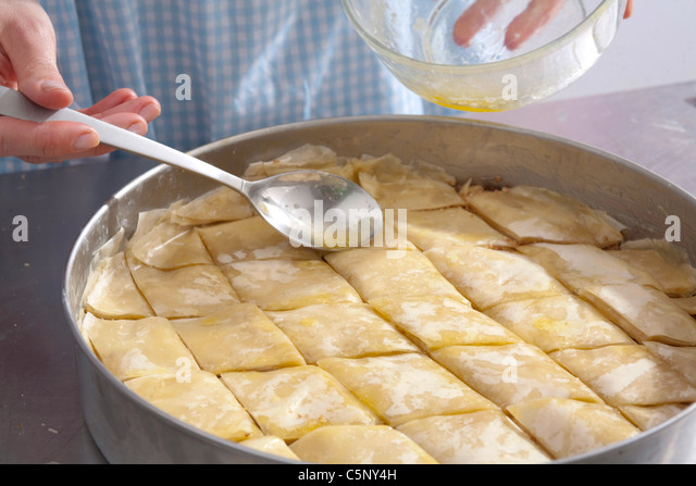 Baklava: spreading top of cake with hot butter - Stock Image