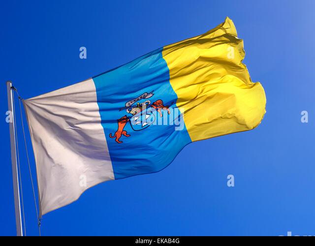 Sunny flag of the Canary Islands fluttering in the breeze with deep clear blue sky behind - Stock-Bilder