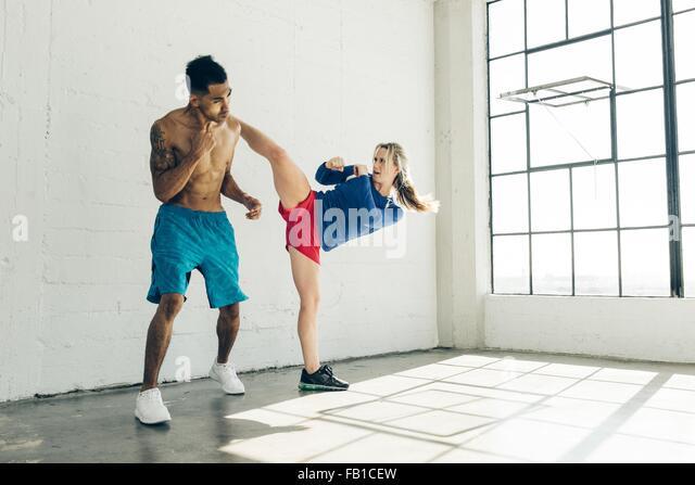 Couple in gym, leg raised, kickboxing - Stock Image