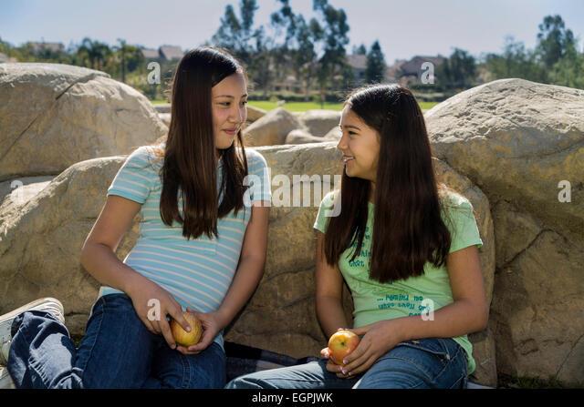 Two Teenage 12-13 year old olds Vietnamese-Caucasian and Hispanic Mexican Caucasian girls talking share fruit. MR - Stock-Bilder